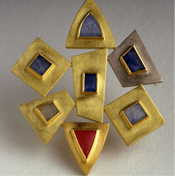Irregular gold shapes in a brooch with stones