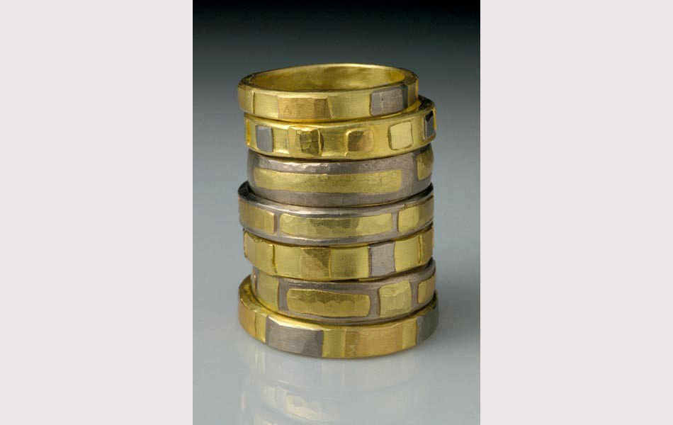 Stack of gold and gray rings