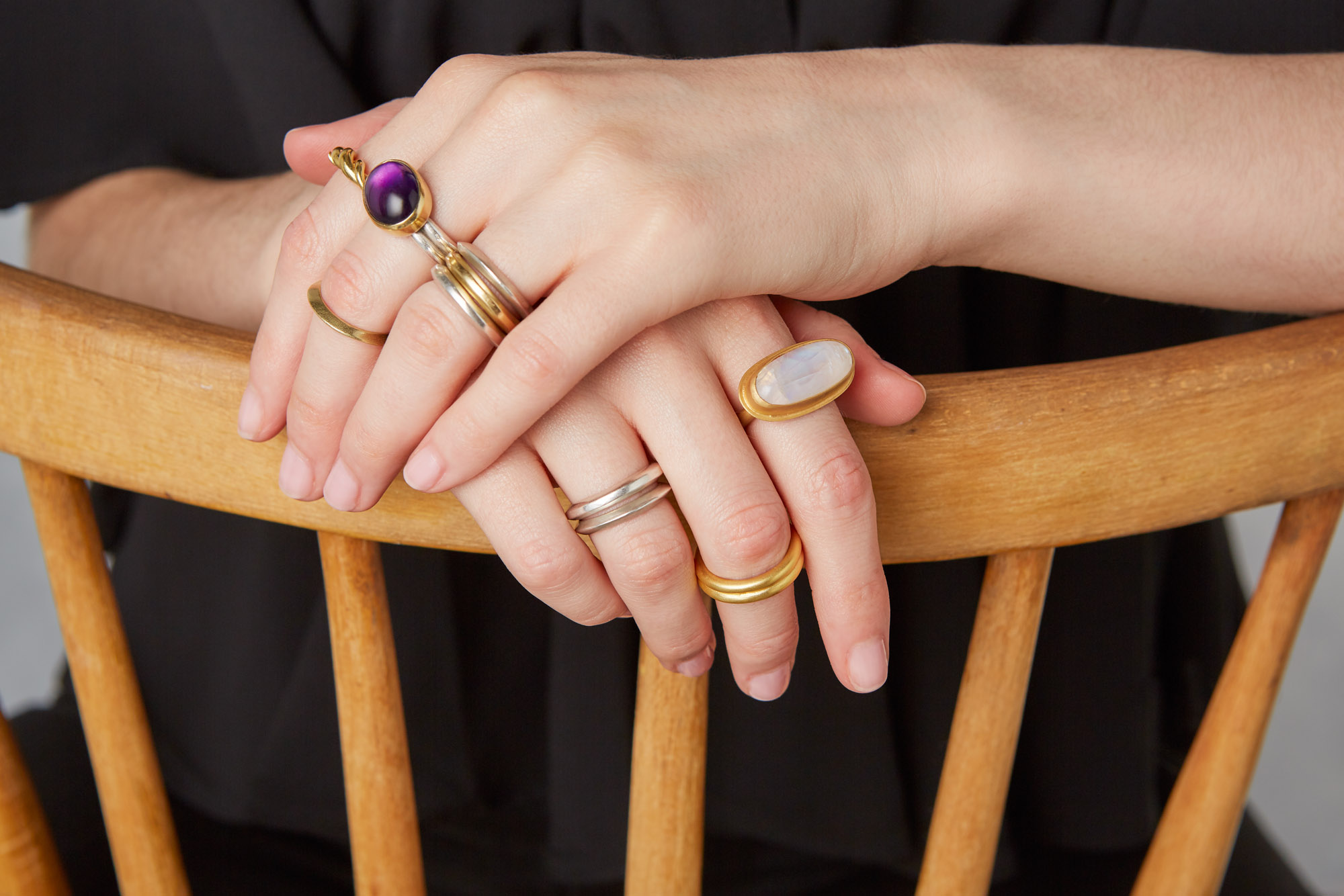 Hands on a chair, wearing rings